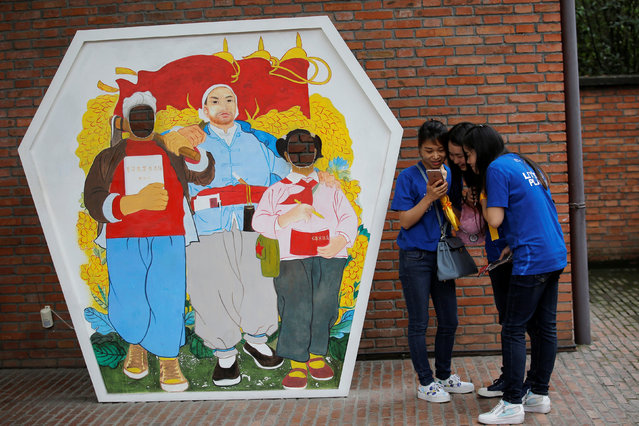 Visitors check their mobile phone after taking a picture with a cut-out depicting an image from a 1960-70s era poster at Jianchuan Museum Cluster in Anren, Sichuan Province, China, May 13, 2016. (Photo by Kim Kyung-Hoon/Reuters)