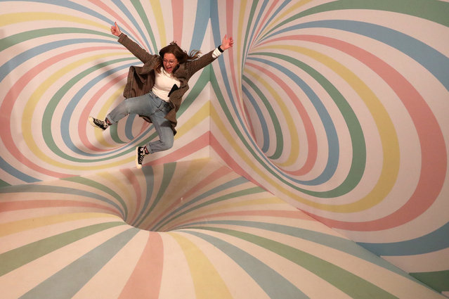 """A girl poses for a photo during a visit to the Instagram museum """"Smile Safari"""" that recently opened in Brussels Belgium on October 4, 2019. (Photo by Yves Herman/Reuters)"""