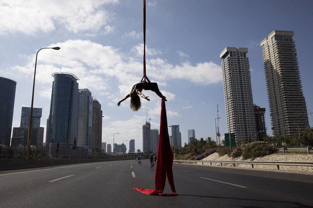 "Israeli acrobat Tel Karassin performs on a car-free highway, during the Jewish holiday of Yom Kippur in Tel Aviv, Israel, Wednesday, October 9, 2019. Israelis are marking Yom Kippur, or ""Day of Atonement"", which is the holiest of Jewish holidays when observant Jews atone for the sins of the past year and the Israeli nation comes to almost a complete standstill. Many residents take bicycles onto the streets as no traffic is permitted on the roads. (Photo by Oded Balilty/AP Photo)"