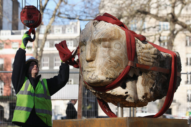 Workmen use a crane to winch a large stone head, created by British sculptor Emily Young, into Berkeley Square