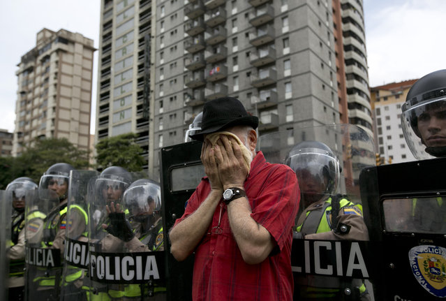 An anti-government demonstrator wipes his face after Bolivarian National Police fired tear gas to block protesters from reaching the headquarters of the national electoral body, CNE, in Caracas, Venezuela, Wednesday, May 18, 2016. The opposition is demanding the government allow it to pursue a recall referendum against Venezuela's President Nicolas Maduro. (Photo by Ariana Cubillos/AP Photo)