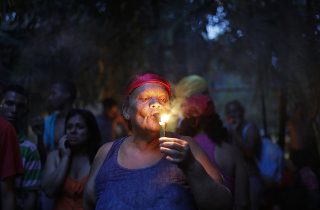 In this photo taken October 11, 2019, a woman lights a cigar at the entrance of Sorte mountain to ask for permission to perform spiritual rituals where followers of indigenous goddess Maria Lionza gather annually in Venezuela's Yaracuy state. Believers congregated for rituals on the remote mountainside where adherents make a pilgrimage to pay homage to the goddess, seeking spiritual connection and physical healing. (Photo by Ariana Cubillos/AP Photo)
