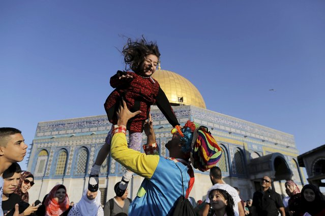 A man dressed as a clown plays with a Palestinian girl on the first day of the Muslim holiday of Eid al-Fitr, which marks the end of the holy month of Ramadan, near the Dome of the Rock at the compound known to Muslims as the Noble Sanctuary and to Jews as Temple Mount, in Jerusalem's Old City, July 17, 2015. (Photo by Ammar Awad/Reuters)