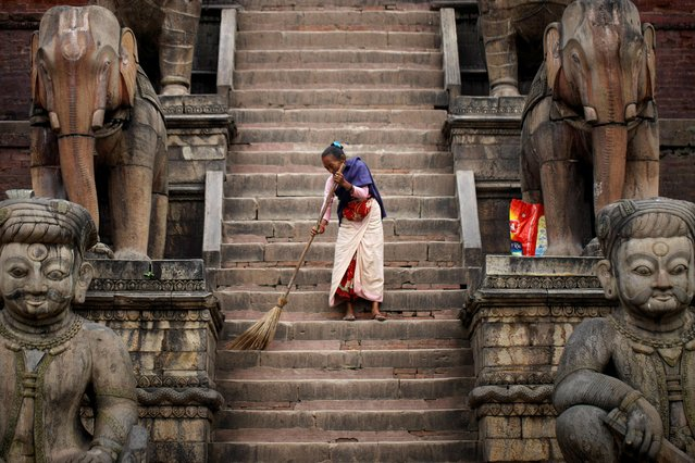 A woman sweeps the premises of Nyatapola Temple in Bhaktapur, Nepal on September 20, 2019. (Photo by Monika Deupala/Reuters)