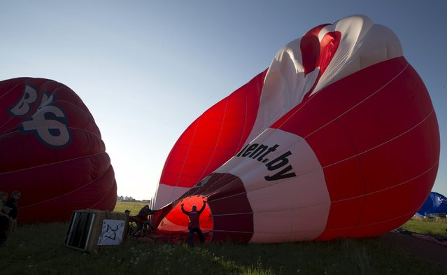 """Participants help inflate a hot air balloon at the Cup Hot Air event during the Air Sports festival titled """"70 Years of Peaceful Sky"""" in Minsk, Belarus July 18, 2015. (Photo by Vasily Fedosenko/Reuters)"""