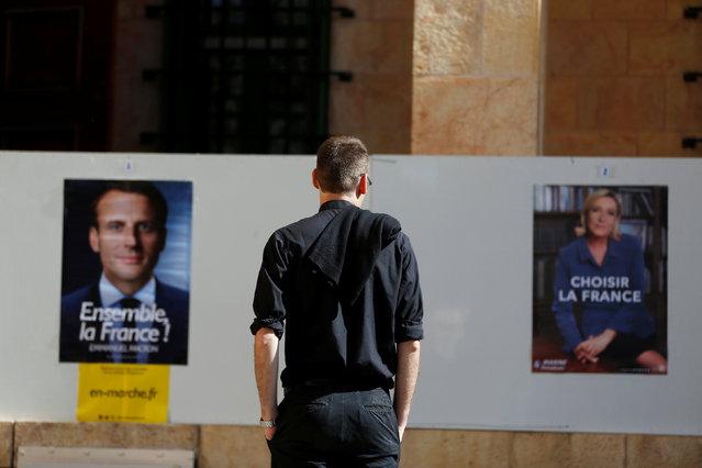 A French national living in Israel looks at posters depicting the candidates of the 2017 French presidential election, Emmanuel Macron and Marine Le Pen, outside a polling station in Jerusalem May 7, 2017. (Photo by Ronen Zvulun/Reuters)