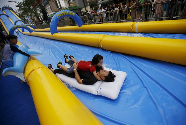 A man holding his daughter enjoys a ride on a 350-meter (1148 feet) long water slide during 2015 City Silde Festa in central Seoul, South Korea, July 19, 2015. (Photo by Kim Hong-Ji/Reuters)