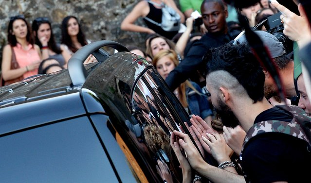 Fans gather near a car at Forte di Belvedere in Florence, on May 24, 2014. (Photo by Tiziana Fabi/AFP Photo)