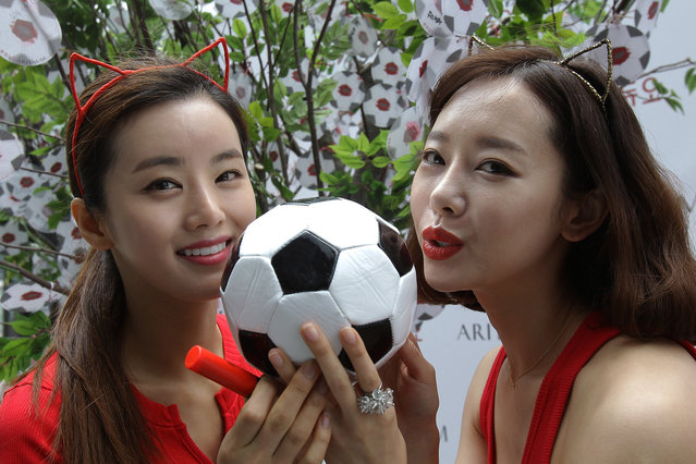 South Korean women kiss the soccer ball during an event wishing for South Korean team's success in the 2014 FIFA World Cup Brazil on June 12, 2014 in Seoul, South Korea. The 2014 FIFA World Cup Brazil will kick off on June 12, 2014. (Photo by Chung Sung-Jun/Getty Images)