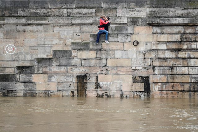 A couple exchanges kisses on the bank as high waters causes flooding along the Seine River in Paris, France, June 1, 2016. (Photo by Charles Platiau/Reuters)