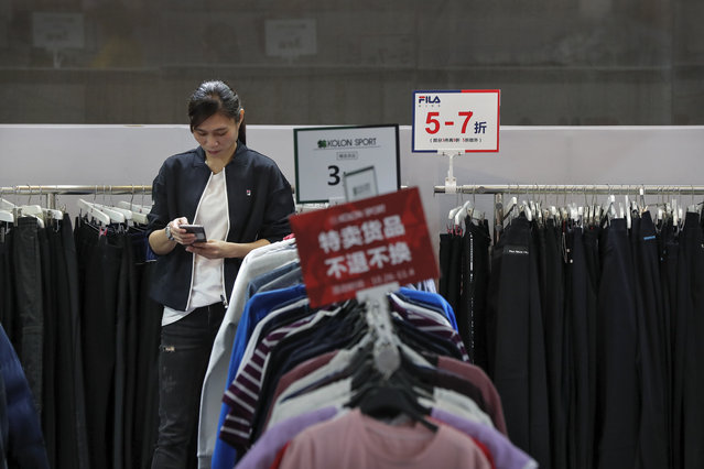 In this November 1, 2019, file photo, an employee browses her smartphone at a clothing store having a promotion sale at a shopping mall in Shenzhen, China's Guangdong province. China has raised its estimate of the size of its economy by 2.1% following a census, raising its gross domestic product for 2018 to 91.93 trillion yuan ($13.1 trillion), the National Bureau of Statistics said Frida, Nov. 22, 2019. (Photo by Andy Wong/AP Photo/File)