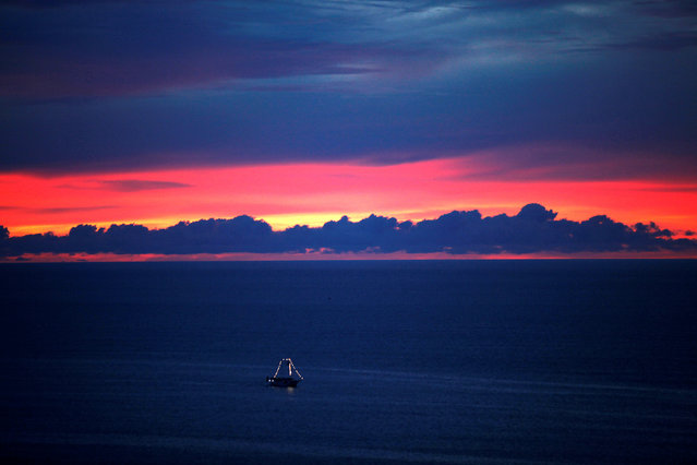 A boat sails during the sunset in the sea of Fortaleza, Brazil, April 23, 2017. (Photo by Paulo Whitaker/Reuters)