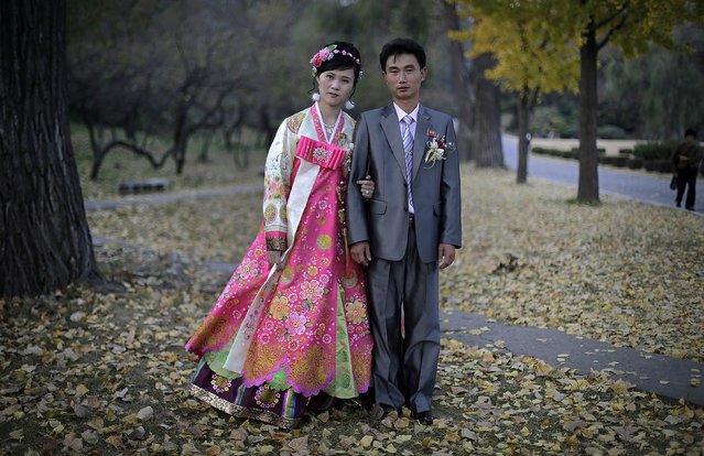 "In this October 25, 2014, file photo, North Korean bride Ri Ok Ran, 28, and groom Kang Sung Jin, 32, pose for a portrait at the Moran Hill where they went to take wedding pictures, in Pyongyang, North Korea. The couple were married after dating for about two years. Their motto: ""To have many children so that they can serve in the army and defend and uphold our leader and country, for many years into the future"". (Photo by Wong Maye-E/AP Photo)"