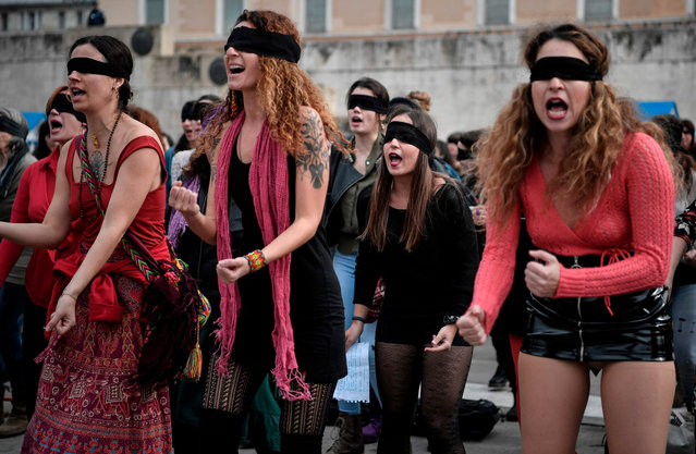 Female activists perform a choreography originated in Chile, and inspired by the Chilean feminist group Las Tesis, to protest against gender violence and patriarchy in front of the Greek parliament at Athens' Syntagma Square on December 22, 2019. (Photo by Louisa Gouliamaki/AFP Photo)