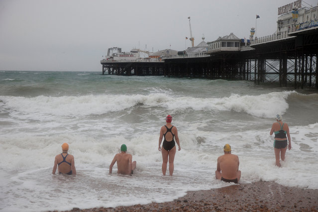 "Brighton, England, 2010. Members of the Sea Swimming Club, who meet daily. Martin Parr writes: ""This is the swimming club in Brighton, who go and swim in the sea every day of the year, regardless of the weather (wet suits are discouraged). You can see, here, the waves were so fierce they were experiencing their own 'Decisive Moment', as they pondered if they dare go into the sea or not. They did eventually sneak in, but a long leisurely dip was not on the cards that particular day"". (Photo by Martin Parr/Magnum Photos)"