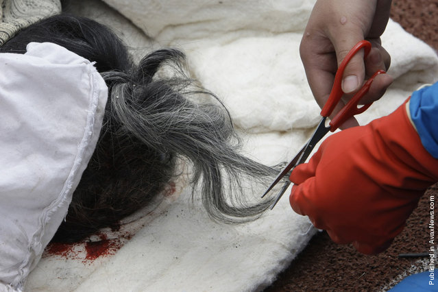 A rescue worker cuts the hair from the body of an elderly woman for identification purposes at the earthquake-hit Hanwang town of Mianzhu county, Sichuan province, May 14, 2008