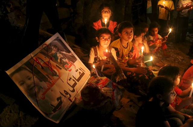 Palestinian children light candles during a rally to remember 18-month-old Palestinian baby Ali Dawabsheh, who was killed after his family's house was set on fire in a suspected attack by Jewish extremists, in Rafah in the southern Gaza Strip August 2, 2015. (Photo by Ibraheem Abu Mustafa/Reuters)