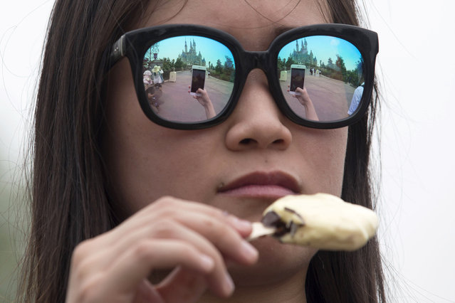 The Disney Resort castle is reflected in the sunglasses of a visitor during a tour on the eve of the opening of the resort in Shanghai, China, Wednesday, June 15, 2016. (Photo by Ng Han Guan/AP Photo)