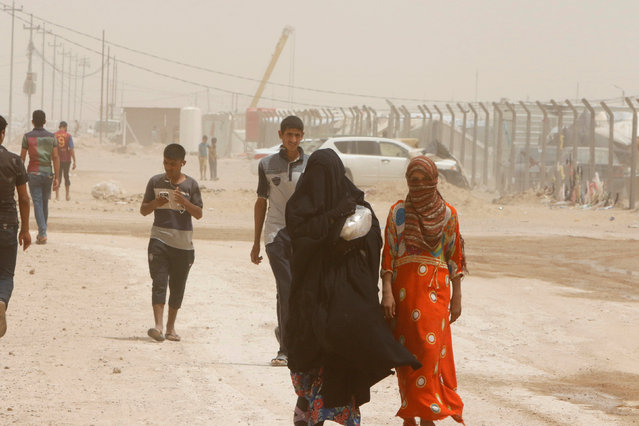 Displaced people, who fled from Falluja because of Islamic State violence, walk during a dust storm at a refugee camp in Ameriyat Falluja, south of Falluja, Iraq, June 16, 2016. (Photo by Ahmed Saad/Reuters)