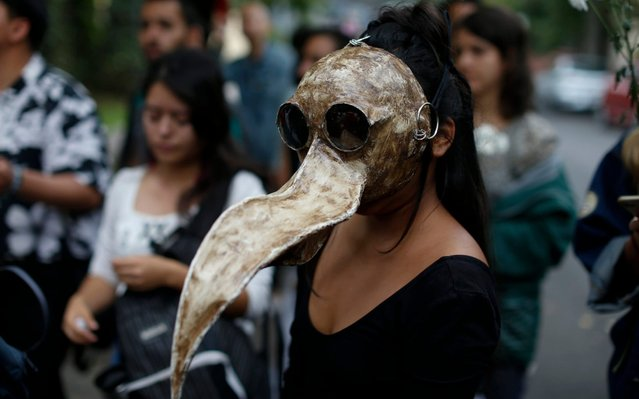 Medical student and environmentalist Sofia Guzman, 22, wears a mask she made to represent a toucan skull, during a protest to call for action to protect the Amazon rainforest, outside Brazil's embassy in Mexico City, Friday, August 23, 2019. Under increasing international pressure to contain fires sweeping parts of the Amazon, Brazil's President Jair Bolsonaro on Friday authorized use of the military to battle the massive blazes. (Photo by Rebecca Blackwell/AP Photo)