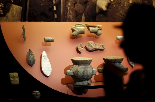 """A visitor looks at pieces used as offerings to the Aztec god Xochipilli, at an exhibition titled """"An Offering to Xochipilli"""" during a media tour at the Museum of the Templo Mayor in Mexico City August 7, 2015. Ancient offerings to the Aztec god Xochipilli which were excavated in Mexico City went on display in the Mexican capital on Friday, revealing new insights into the little-known god of art. (Photo by Henry Romero/Reuters)"""