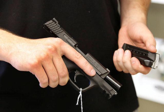 "Salesman Ryan Martinez hold an Smith & Wesson handgun and magazine at the ""Ready Gunner"" gun store in Provo, Utah, U.S., June 21, 2016. (Photo by George Frey/Reuters)"