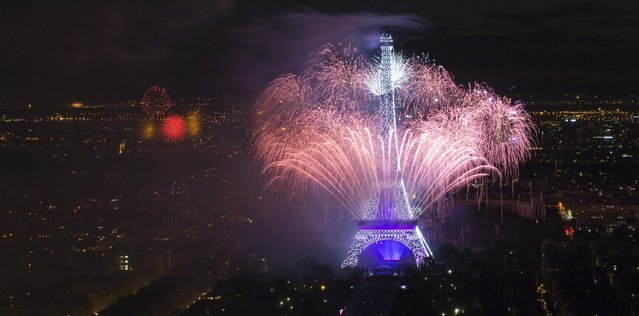 """Fireworks light the sky near the Eiffel Tower in a show called """"Guerre et Paix"""" (War and Peace) as part of events to mark the centenary of the First World War  and to end the traditional Bastille Day celebrations in Paris, July 14, 2014. (Photo by Gonzalo Fuentes/Reuters)"""