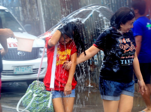 "A man throws water at pedestrians as residents join in a water-splashing frenzy to honor their patron Saint John the Baptist's Feast Day in San Juan, Metro Manila, Philippines June 24, 2016. San Juan is renowned for its celebration of the Nativity of St. John the Baptist every year of June 24. In a nod to the saint's characteristic act, San Juaneños engage in Basaan (""wetting""), where revellers splash people with water. (Photo by Romeo Ranoco/Reuters)"