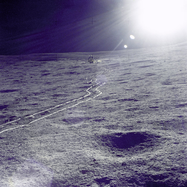 "The Apollo 14 Lunar Module (LM) ""Antares"" is photographed against a brilliant sun glare during the first extravehicular activity (EVA-1). A bright trail left in the lunar soil by the two-wheeled Modularized Equipment Transporter (MET) leads from the LM. (Photo by NASA)"