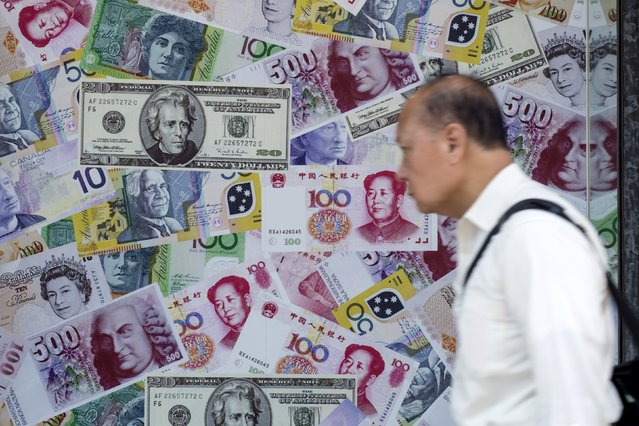 A man walks past an advertisement promoting China's renminbi (RMB) or yuan, U.S. dollar and Euro exchange services at foreign exchange store in Hong Kong, China, August 13, 2015. German Bund yields edged up on Thursday following efforts by China's central bank to slow a sharp descent of the yuan that has prompted investors this week to seek safe-haven assets. (Photo by Tyrone Siu/Reuters)