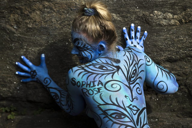 Debbie McCabe, of New Jersey, poses after being painted at Columbus Circle as body-painting artists gathered to decorate nude models as part of an event featuring artist Andy Golub, Saturday, July 26, 2014, in New York. Golub says New York was the only city in the country that would allow his inaugural Bodypainting Day. (Photo by John Minchillo/AP Photo)