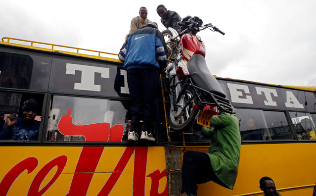 Loaders push a motorcycle atop a public bus for passengers traveling to the countryside ahead of next week's general election in Nairobi, Kenya on August 3, 2017. (Photo by Thomas Mukoya/Reuters)
