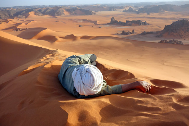 """A Well Earned Rest in the Sahara"". This photo of Moussa Macher, our Tuareg guide, was taken at the summit of Tin-Merzouga, the largest dune (or erg) in the Tadrat region of the Sahara desert in southern Algeria. Moussa rested while waiting for us to finish our 45-minute struggle to the top. Photo location: Summit of Tin-Merzouga, Tadrat, Tassili N'Ajjer National Park, Algeria. (Photo and caption by Evan Cole/National Geographic Photo Contest)"