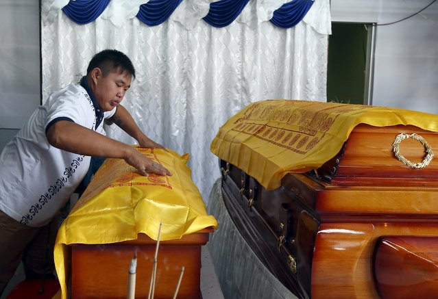 A family member places a cloth over 4-year-old Lee Jing Xuan's coffin, after she and her father Lee Tze Siang were killed in Monday's deadly blast in Bangkok, Thailand, at their home in Butterworth, Malaysia, August 20, 2015. (Photo by Olivia Harris/Reuters)