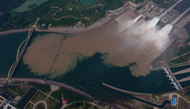 This aerial view shows water being released from the floodgates of the Xiaolangdi dam on the Yellow River near Luoyang, in China's Henan province on June 29, 2016. The floodgates are opened every year in an operation to flush millions of tonnes of silt from the river bed. (Photo by AFP Photo/Stringer)
