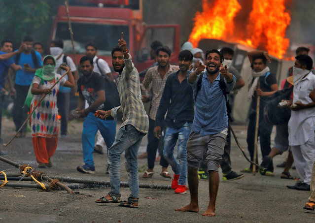 People react during violence in Panchkula, India, August 25, 2017. (Photo by Cathal McNaughton/Reuters)