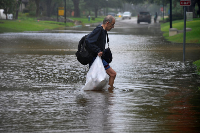 A man carries his belongings through flood waters in Houston, Texas on August 28, 2017. (Photo by Nick Oxford/Reuters)