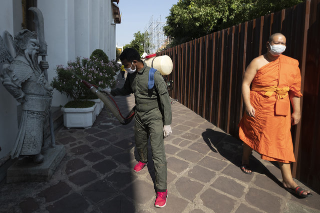 A Buddhist monk wears a protective mask as a worker sprays disinfectant at Wat Pho temple in Bangkok, Thailand, Friday, March 13, 2020. For most people, the new coronavirus causes only mild or moderate symptoms. For some it can cause more severe illness. (Photo by Sakchai Lalit/AP Photo)