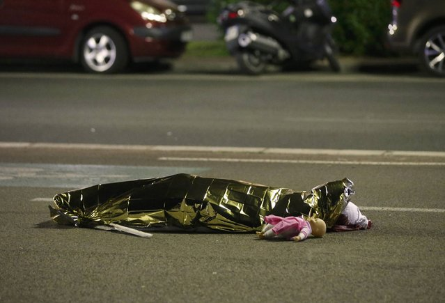 A body is seen on the ground July 15, 2016 after at least 30 people were killed in Nice, France, when a truck ran into a crowd celebrating the Bastille Day national holiday July 14. (Photo by Eric Gaillard/Reuters)