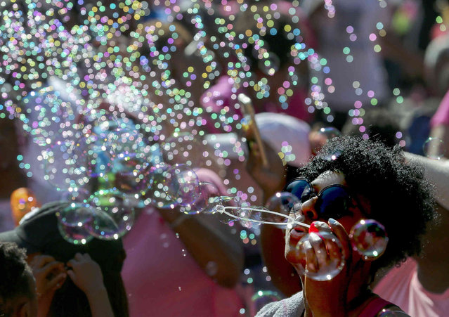 """Trinity Newman blows bubbles along with thousands of people outside City Hall in honor of Maleah Davis, the four-year-old girl who went missing in early May and whose body was found tossed along an Arkansas roadside last week, on Sunday, June 9, 2019, in Houston. The city declared today """"Maleah Davis Day"""" and people wore pink, her favorite color, in her honor. (Photo by Godofredo A Vásquez/Houston Chronicle via AP Photo)"""