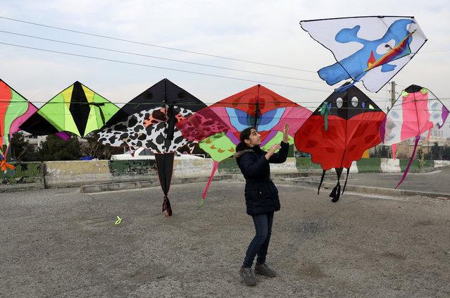 A girl flies a kite at Pardisan Park in Tehran, Iran, Friday, February 28, 2020. (Photo by Vahid Salemi/AP Photo)