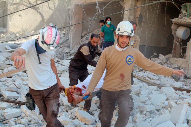 Civil defence members carry an injured man amid rubble of damaged buildings after an airstrike on Aleppo's rebel held al-Fardous district, Syria July 16, 2016. (Photo by Abdalrhman Ismail/Reuters)