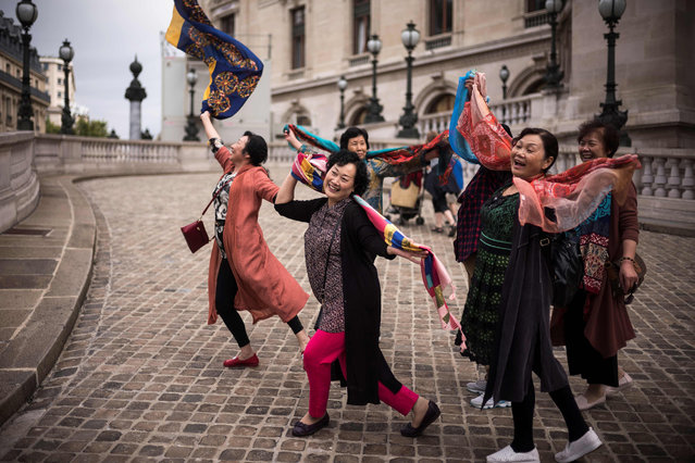 Asian tourists pose for pictures in front of the Opera Garnier in Paris on September 4, 2017. (Photo by Lionel Bonaventure/AFP Photo)