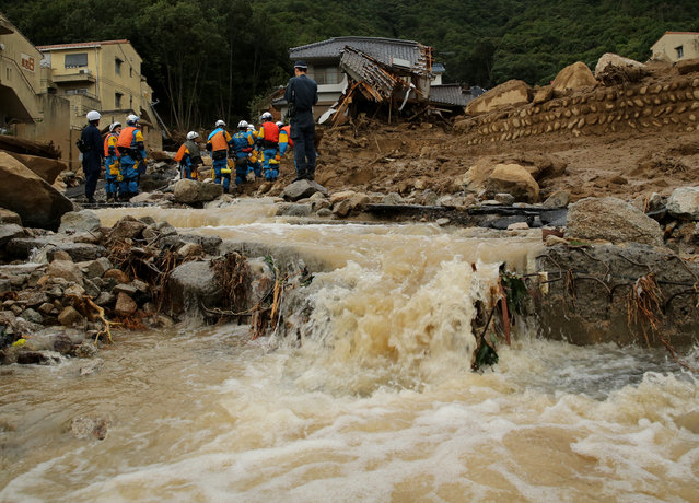 Members of police continue the search for missing people among the debris of houses destroyed by a landslide caused by torrential rain at the site of a landslide in a residential area on August 20, 2014 in Hiroshima, Japan. (Photo by Buddhika Weerasinghe/Getty Images)
