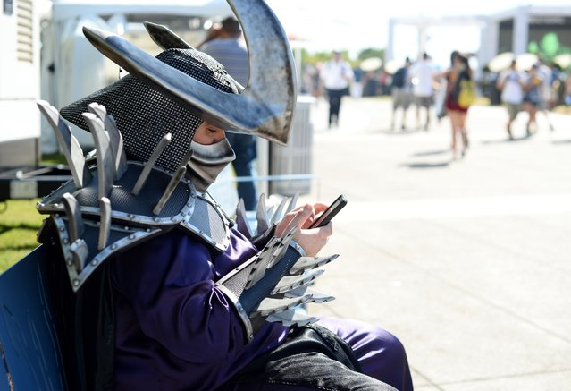 A fan dressed as Super Shredder checks his Instagram on day 2 of Comic-Con International on Friday, July 22, 2016, in San Diego. (Photo by Al Powers/Invision/AP Photo)