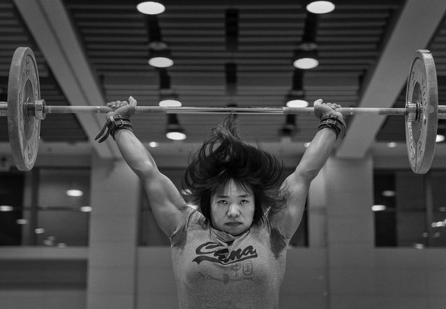 Chinese female weightlifter Xiang Yanmei, who competes in the 69 kg weightclass, rests with a weight on her stomach as she checks her phone during a training session in preparation for the Rio Olympics at the Training Center of General Administration of Sports in China on July 20, 2016 in Beijing, China. Xiang Yanmei won the World Championships in 2013 and 2015. (Photo by Kevin Frayer/Getty Images)