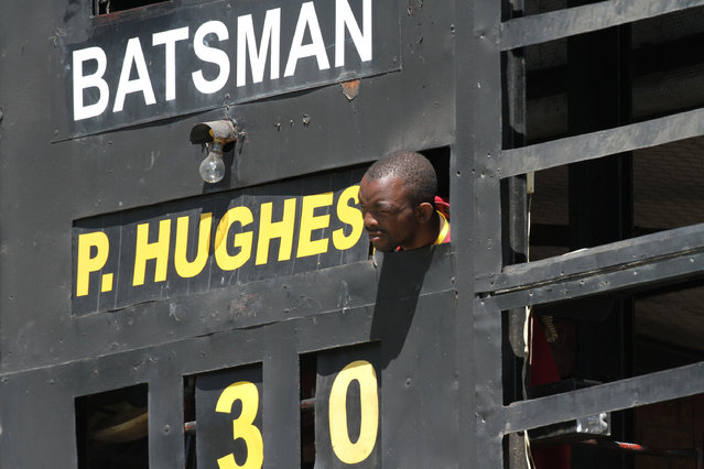A scoreboard operator watches the match from behind the board during the cricket One Day International between South Africa and Australia in Harare Zimbabwe Tuesday, September 2, 2014. (Photo by Tsvangirayi Mukwazhi/AP Photo)