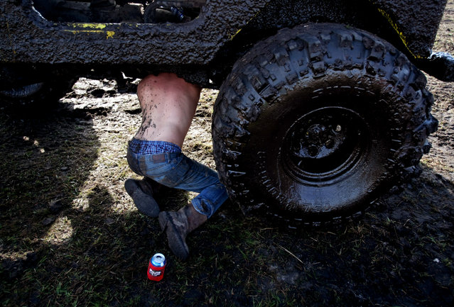 Paul Lambert of Deland repairs a twisted universal joint on his jeep. (Photo by Gary Coronado/The Palm Beach Post)
