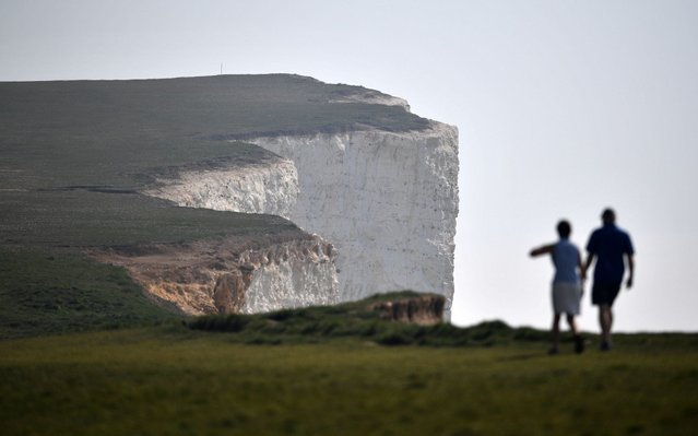 "People walk along Beachy Head, close to Eastbourne on the south coast of England on April 12, 2020, as life in Britain continues over the Easter break, during the nationwide lockdown to combat the novel coronavirus pandemic. Britain's Prime Minister Boris Johnson was making ""very good progress"" on Saturday in his recovery in hospital from coronavirus, officials said, as the country's deaths toll from the disease approached the grim milestone of 10,000. (Photo by Ben Stansall/AFP Photo)"