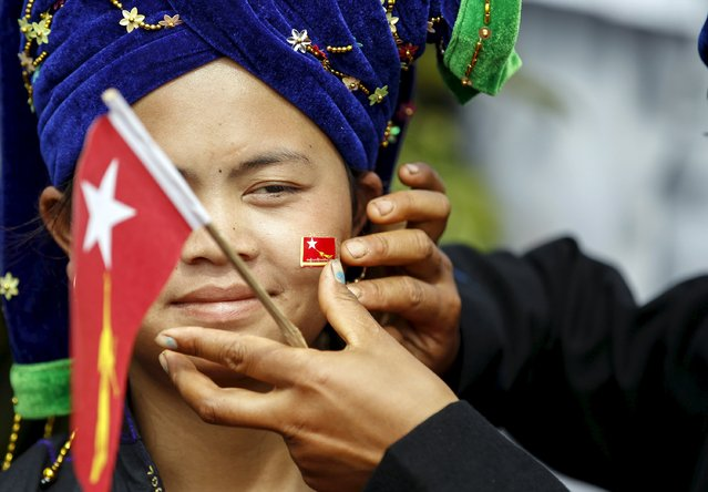 An ethnic Pa'O woman has a National League for Democracy party flag put on her cheek as she waits for Myanmar pro-democracy leader Aung San Suu Kyi to arrive to give a speech on voter education at the Hsiseng township in Shan state, Myanmar September 5, 2015. (Photo by Soe Zeya Tun/Reuters)